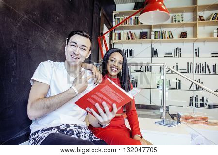couple students in univercity library, looking book, preparing to exam, having fun, making selfie, lifestyle people concept