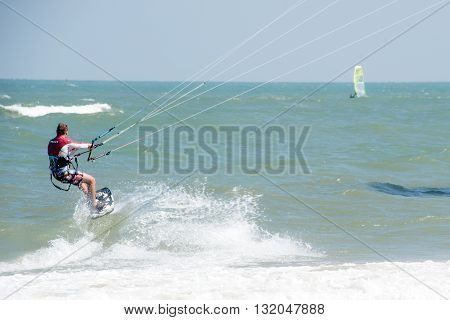 PHRACHUAP KHIRI KHUN,THAILAND-DECEMBER 20,2013 : Unidentified Kite surfer in action at Phranburi sea near Phranburi District. Preparation starting from the beach on Decemberb 20,2013,Phrachuap Khiri Khun ,Thailand.
