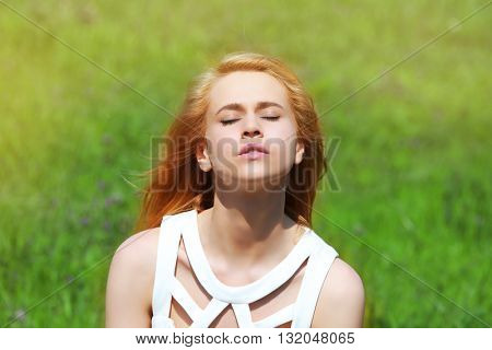 Young beautiful woman on green grass background