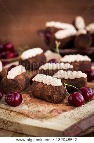 Chocolate rum balls cakes decorated with cream and fresh cherry