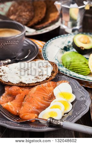 Breakfast with salted salmon boiled eggs avocado bread cream cheese and coffee