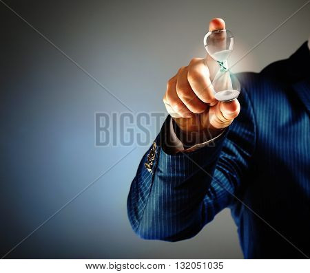 Businessman holding hourglass in hand on grey background