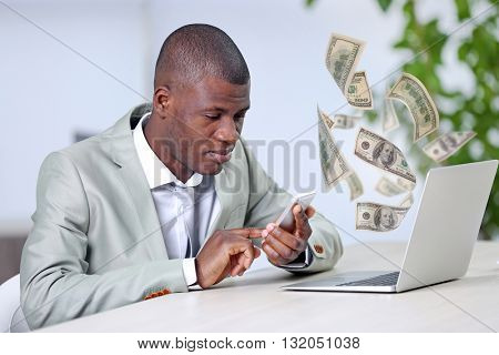 Financial concept. Make money on the Internet. African American businessman working with laptop