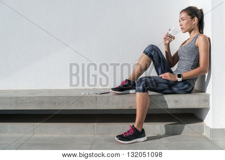 Fitness athlete woman drinking water during cardio workout break Healthy living hydration concept. Runner woman preventing dehydration for her health and body by hydrating on summer outdoors training.