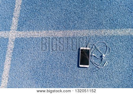 Running track and field lane and smartphone for music listening on mobile phone app with earphones earbuds. Blue background texture of tracks lanes for copyspace for fitness and sports concepts.
