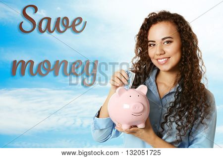 Beautiful young girl holding piggy bank on blue sky background