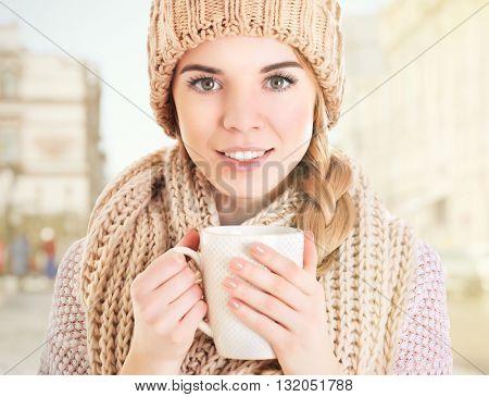Beautiful girl enjoying a cup of tea on blurred urban background