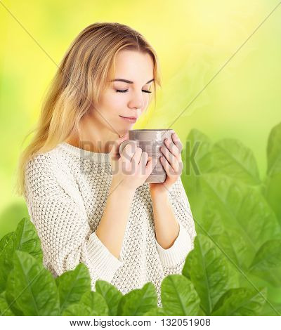 Beautiful girl enjoying a cup of tea on blurred green nature background
