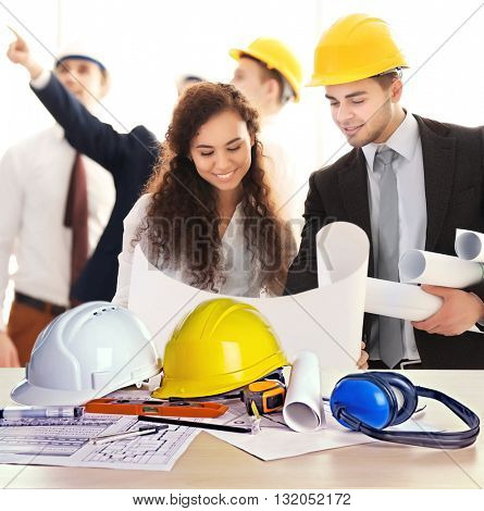 Table with construction drawings and few engineers with blueprint in office
