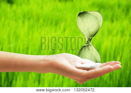 Hourglass in female hand on green grass background