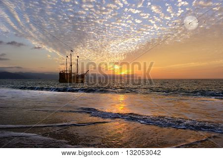 Pirate ship fantasy is an old wooden pirate ship with full flags as the sun sets on the ocean and the moon rises in a colorful sunset sky.