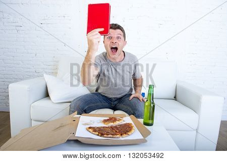 young man alone holding notepad showing it as referee red card in angry face expression in stress watching football game on television at home couch with pizza box and beer bottle screaming excited