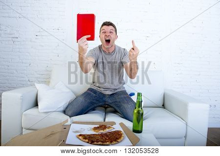 young man alone holding notepad showing it as referee red card in angry face giving the finger in stress watching football game on television at home couch with pizza box and beer bottle screaming