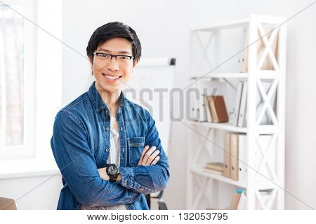 Happy handsome asian young businessman standing with arms crossed in office