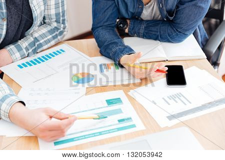 Top view of two businesspeople sitting and working at the table in office