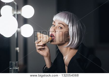 Tempting tender young woman in blonde wig eating pizza and drinking champagne sitting near the mirror