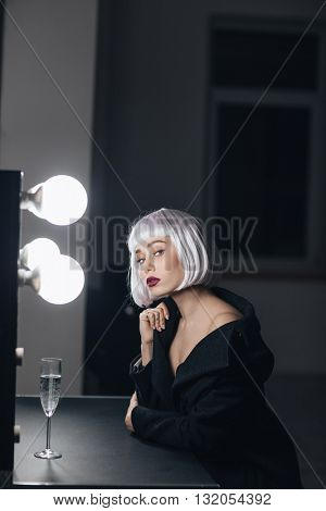 Portrait of alluring blonde young woman drinking champagne in dressing room