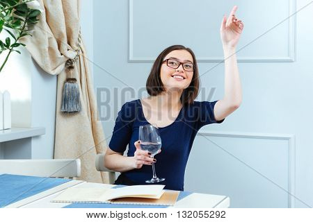Happy lovely young woman in glasses with glass of water sitting and calling for waitress in cafe
