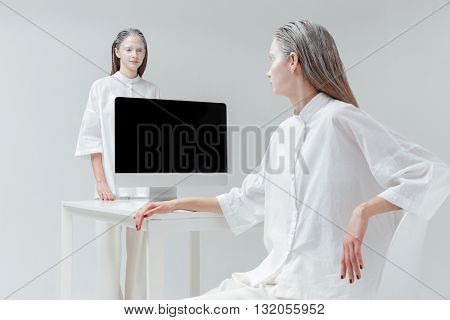 Two young beautiful fashion women looking at each other at the desk with computer, pc over gray background