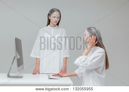 Two alien cosmic women using computer over gray background