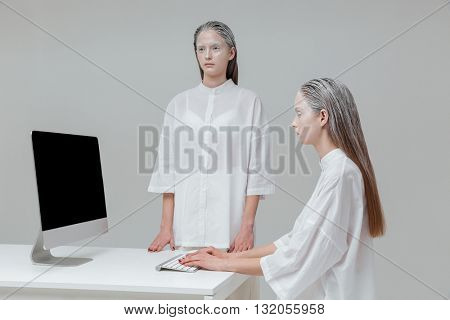 Two mysterious fashion girls using computer, pc