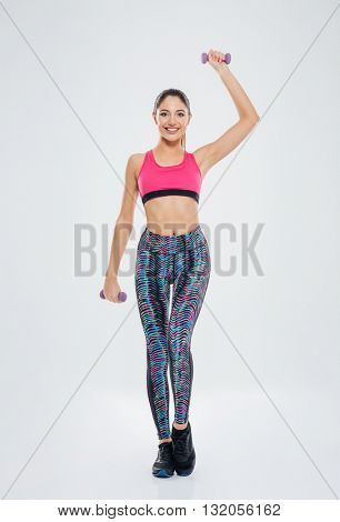 Full length portrait of a happy fitness woman lifting dumbbells isolated on a white background