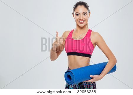 Happy fitness woman holding yoga mat and showing thumb up isolated on a white background