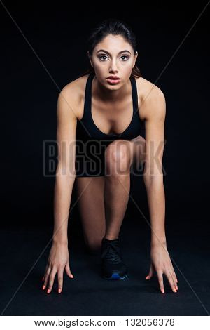 Full length portrait of a sports woman reading to run on black background