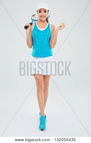 Full length portrait of a smiling female tennis player standing isolated on a white background and looking at camera