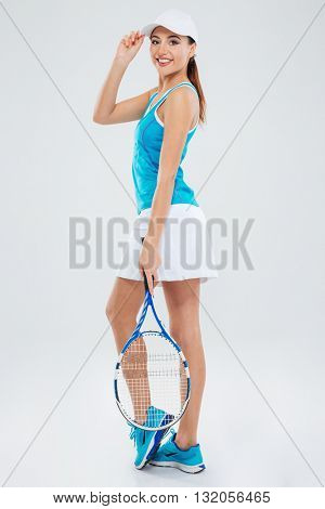 Full length portrait of a happy female player looking back at camera isolated on a white background