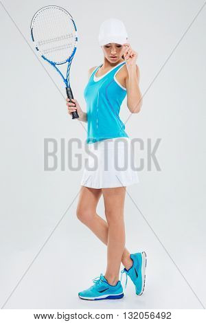 Full length portrait of a female tennis player posing isolated on a white background
