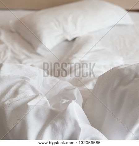 bed in a hotel room with unfolded quilt in the morning