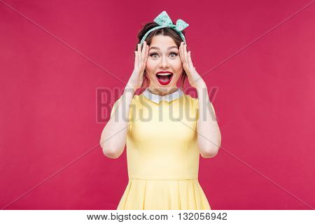 Portrait of cheerful beautiful pinup girl with hands touching her face over pink background