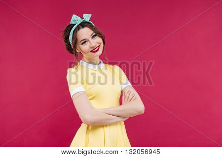 Smiling beautiful young woman in yellow dress standing with arms crossed over pink background
