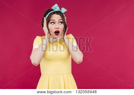 Scared pretty pinup girl in yellow dress standing with hands on head over pink background