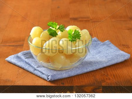 bowl of small pickled onions with parsley on blue napkin