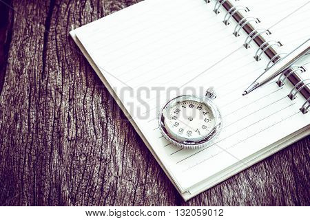Pocket watch on notebook for notes On old textured wood. Vintage style.
