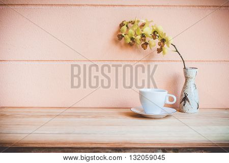 orchid flowers in vase and coffee cup on a wooden table.