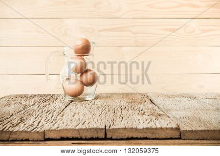 Eggs in glass on old wooden table.
