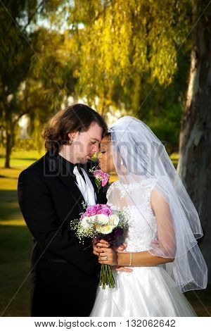 A newly wed couple leans together with foreheads pressed against each other. Their eyes are closed as they take a moment to reflect on their wedding day. She is holding her bouquet and he is holding her.
