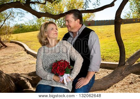 A couple celebrates their anniversary. The wife holds a rose bouquet to symbolize her wedding flowers. They gaze into each others eyes and she tries not to laugh.