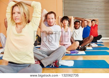 People stretching during fitness class in fitness center