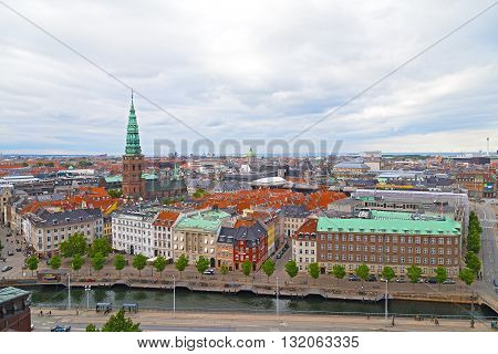 Panorama of colorful roof tops and old churches in Copenhagen Denmark. City roof tops on a cloudy summer morning.