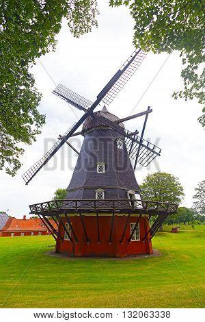Beautiful old windmill in Copenhagen Denmark. Traditional Danish wooden windmill on the green field.