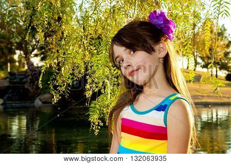 A young girl with a big purple floor in her hair stands by a lake with a slight smirk.