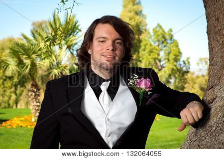 A groom leans on a tree on his wedding day. He has a pink rose boutonniere a white vest and tie silver diamond shaped earrings and long hair.