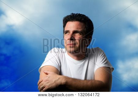 A handsome man looks off in the distance against a blue slightly cloudy sky. He is wearing a white t-shirt and is lit from the side. His wedding ring is prominent. He looks serious intense determined hopeful.