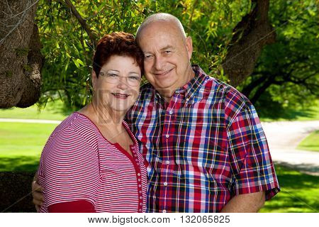 A happy senior couple poses for the camera holding each other smiling.