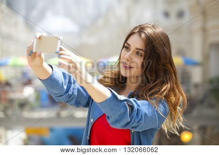 Beautiful, smiling brunette woman take a picture of herself with a smartphone. selfie, indoors shot, horizontal