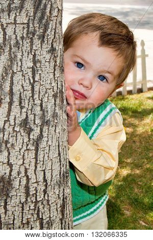 A well dressed little boy with a very messy face and big blue eyes peeks around from behind a tree with a solemn facial expression.